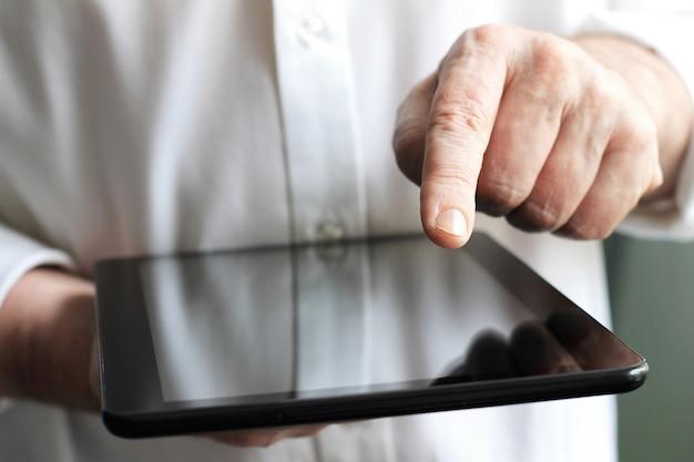Homem negócios, com, dedo, tela tocante, de, um, tablete digital, enquanto