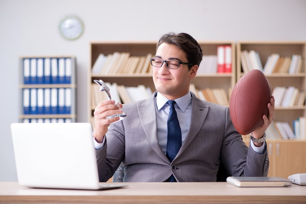 Homem negócios, com, futebol americano, em, escritório