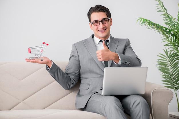 Homem negócios, com, laptop, e, carrinho de compras