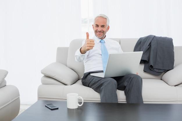 Homem negócios, com, laptop, gesticule, polegares cima, casa
