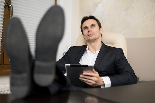 Homem negócios, com, pernas, escrivaninha, em, escritório