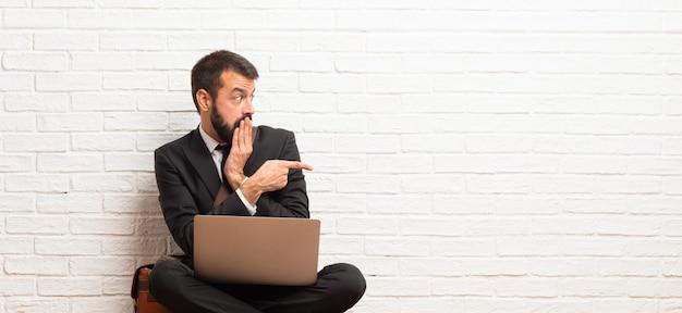 Homem negócios, com, seu, laptop, sentar chão, apontar, dedo, para, a, lado, com, um, surpreendido, rosto