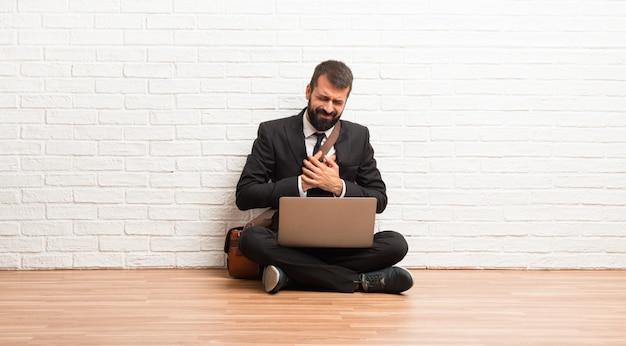 Homem negócios, com, seu, laptop, sentar chão, tendo, um, dor, coração