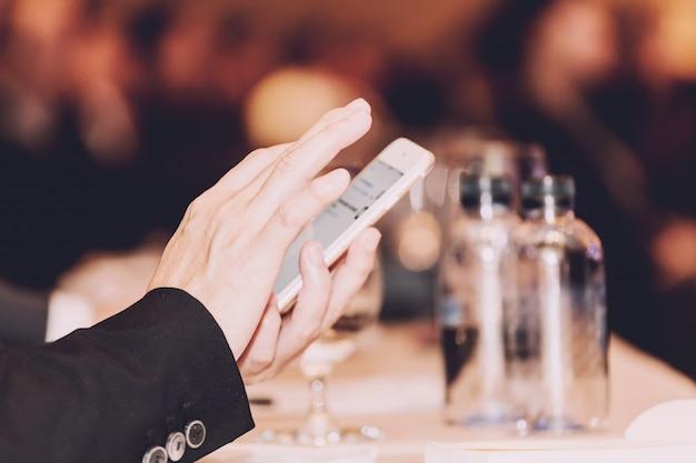Homem negócios, com, seu, smartphone, em, seminário, sala