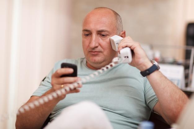 Homem negócios, em, escritório, falando, ligado, dois telefones