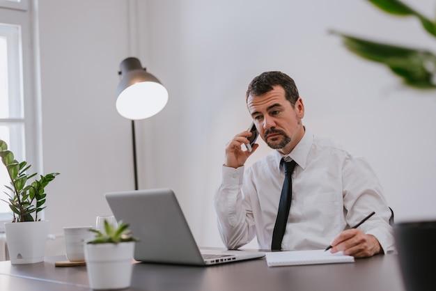 Homem negócios, em, escritório, falando telefone