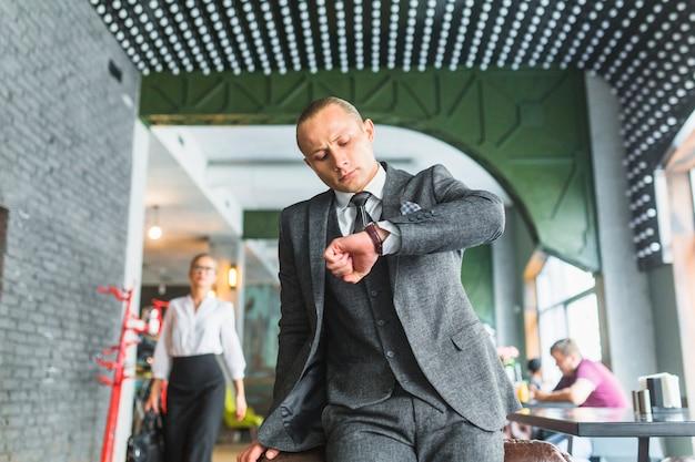 Homem negócios, em, paleto, tempo verificando, ligado, seu, relógio pulso, em, restaurante