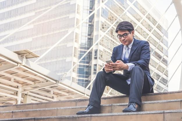 Homem negócios, em, paleto, usando, smartphone, em, cidade