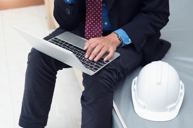 Homem negócios, engenharia, trabalhando, com, laptop, e, capacete, em, sala