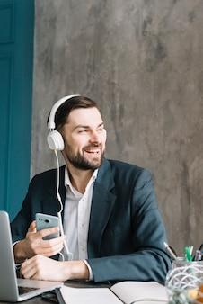 Homem negócios, escutar música, e, olhando