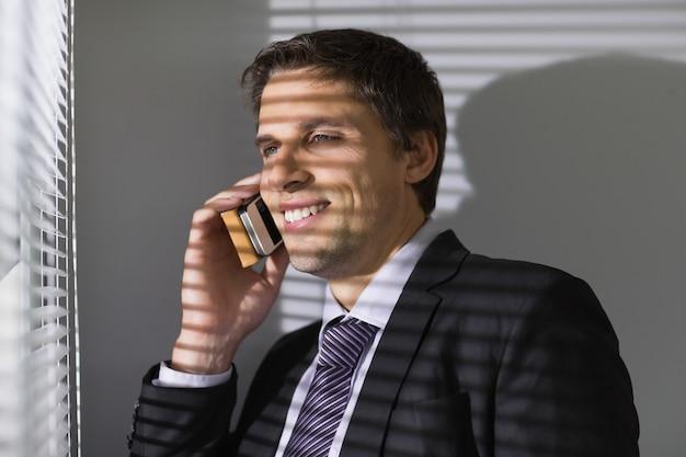 Homem negócios, espreitar, através, venezianas, enquanto, chamada, em, escritório