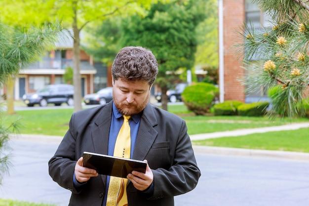 Homem negócios, exterior, escritório homem, comprando online, com, um, cartão crédito, e, um, tabuleta, em, a, rua