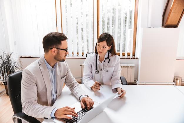 Homem negócios, falando, com, doutor feminino, em, a, hospitalar