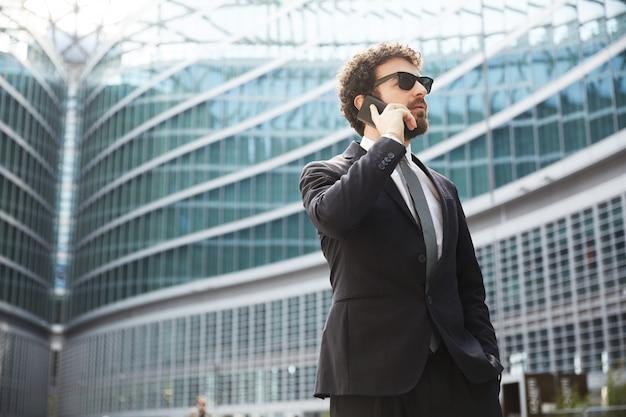 Homem negócios, falando, para, móvel, em, urbano, cidade