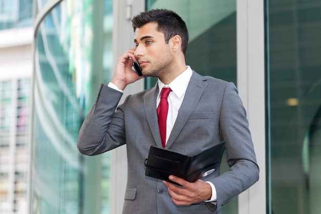 Homem negócios, falando telefone, enquanto, notas leitura