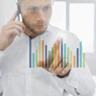 Homem negócios, fazendo, telefonema, e, olhar, gráficos