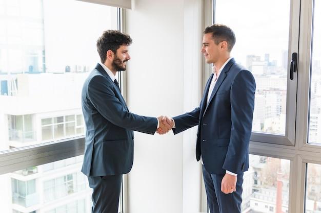 Homem negócios fica, em, escritório, perto, a, janela apertando mãos