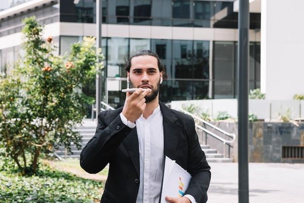 Homem negócios fica, exterior, a, edifício escritório, falando, ligado, viva-voz, telefone móvel