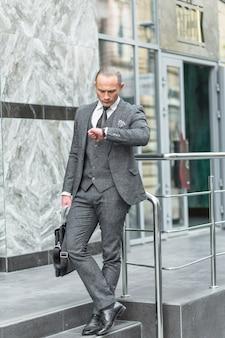 Homem negócios fica, ligado, escadaria, tempo verificando, ligado, relógio pulso