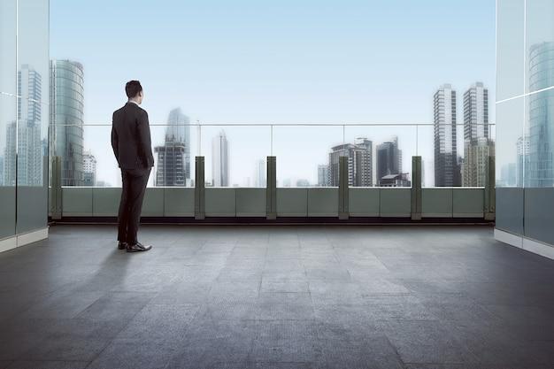 Homem negócios fica, ligado, um, telhado, e, olhar, cidade