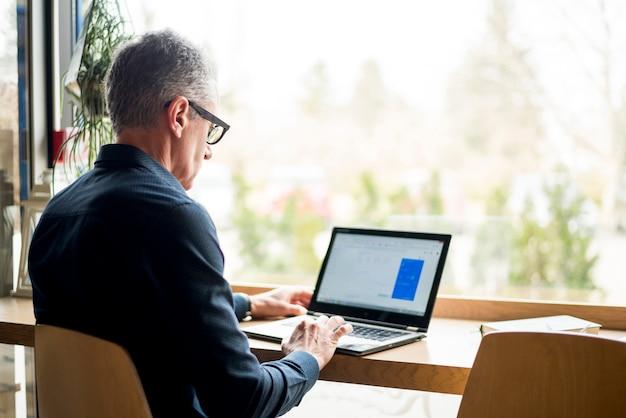 Homem negócios idoso, usando computador portátil