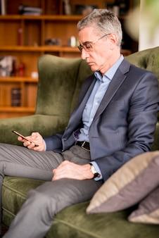 Homem negócios idoso, usando, telefone móvel