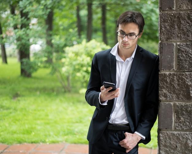 Homem negócios, inclinar-se parede, e, verificar, telefone