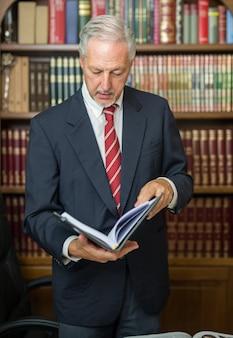 Homem negócios, lendo um livro, em, um, biblioteca