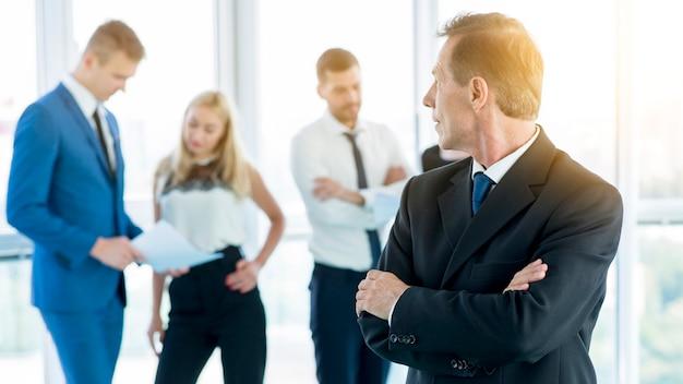 Homem negócios maduro, com, braços dobrados, olhar, seu, colegas, em, escritório