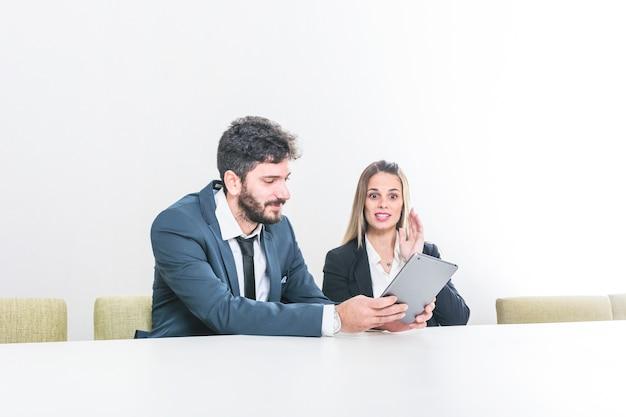 Homem negócios, mostrando, tablete digital, para, dela, colega, sentando, em, reunião diretoria
