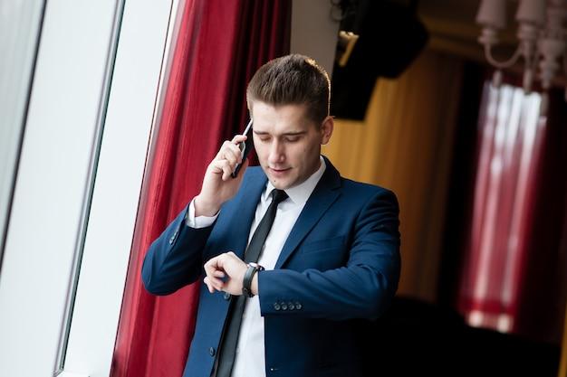 Homem negócios, olhando relógio, e, conversa telefone