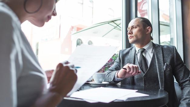 Homem negócios, olhar através janela, enquanto, seu, sócio, trabalhar, ligado, documento, em, caf�