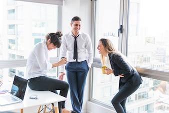 Homem negócios, olhar, dois, executiva, rir, em, escritório