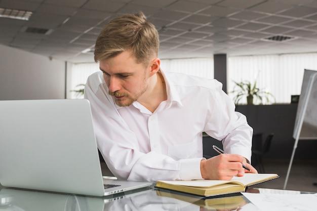 Homem negócios, olhar, laptop, enquanto, escrita, cronograma, em, diário