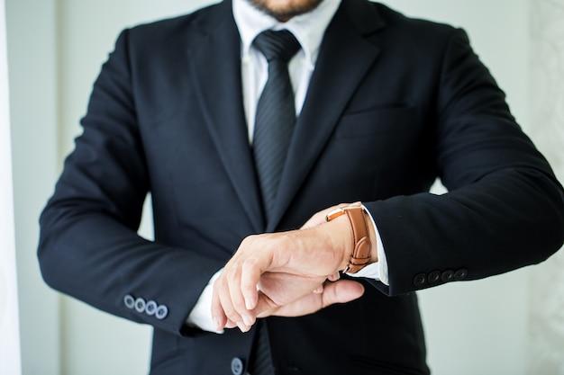 Homem negócios, olhar, seu, relógio, em, escritório