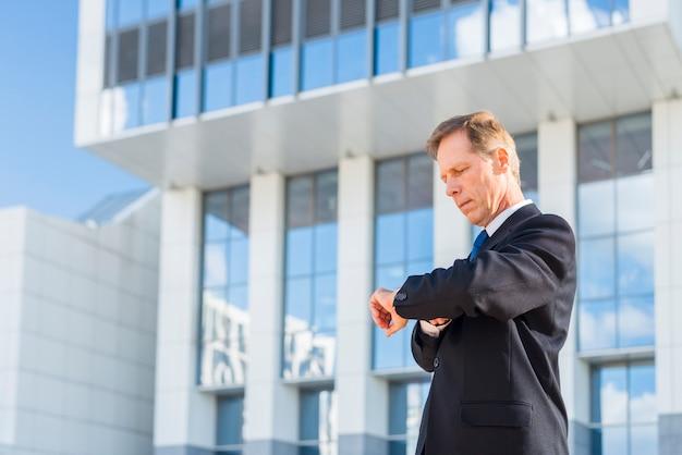 Homem negócios, olhar, tempo, frente, predios