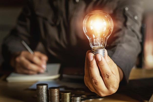 Homem negócios, segurando, bulbo leve, com, dinheiro, stack.saving, poder energia, conceito