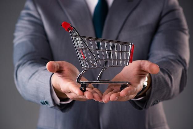 Homem negócios, segurando, carrinho de compras, em, negócio, conceito