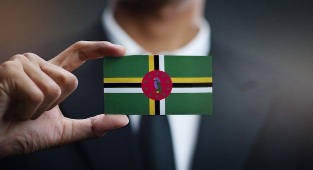 Homem negócios, segurando, cartão, de, dominica, bandeira