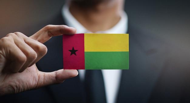 Homem negócios, segurando, cartão, de, guiné-bissau, bandeira