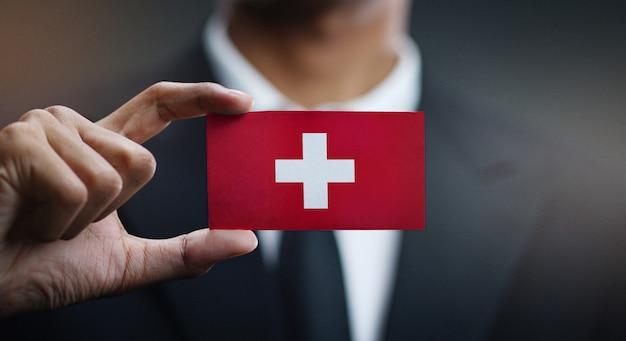 Homem negócios, segurando, cartão, de, suíça, bandeira