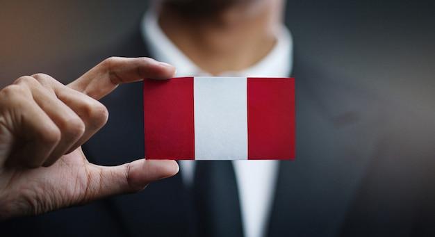 Homem negócios, segurando, cartão, peru, bandeira