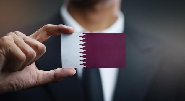 Homem negócios, segurando, cartão, qatar, bandeira
