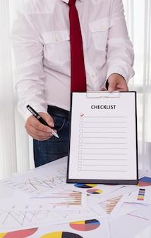 Homem negócios, segurando clipboard, com, checklist, contra