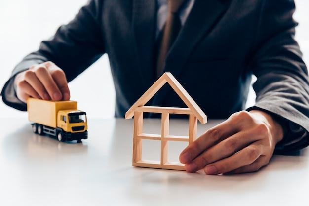 Homem negócios, segurando, miniatura, de, casa, e, caminhão entrega, para, em movimento