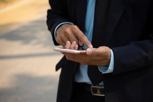 Homem negócios, segurando, móvel, esperto, telefone, e, usando, esperto, telefone, para, negócio, conexão