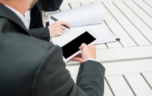 Homem negócios, segurando, smartphone, em, mão, sentando, com, seu, colega, segurando caneta, sobre, a, documento