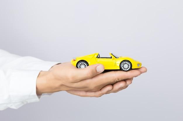 Homem negócios, segurando, um, car brinquedo, isolado, fundo
