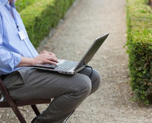 Homem negócios, segurando, um, laptop, ligado, seu, joelhos