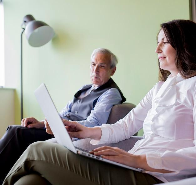 Homem negócios sênior, olhar, mulher, trabalhar, laptop